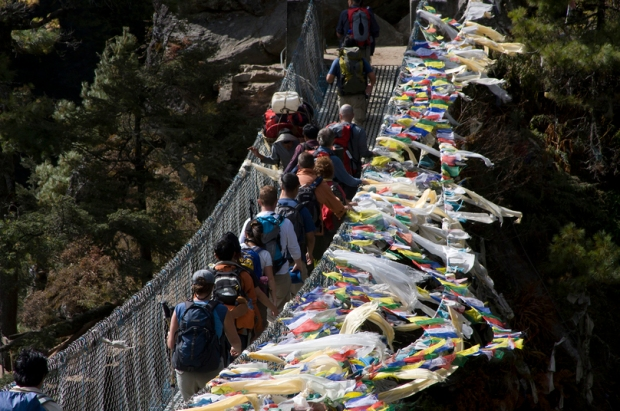 trekkers cross a bridge with prayer flags, Solu Khumbu (Everest) Region, Sagarmatha National Park, Himalaya, Nepal, South Asia